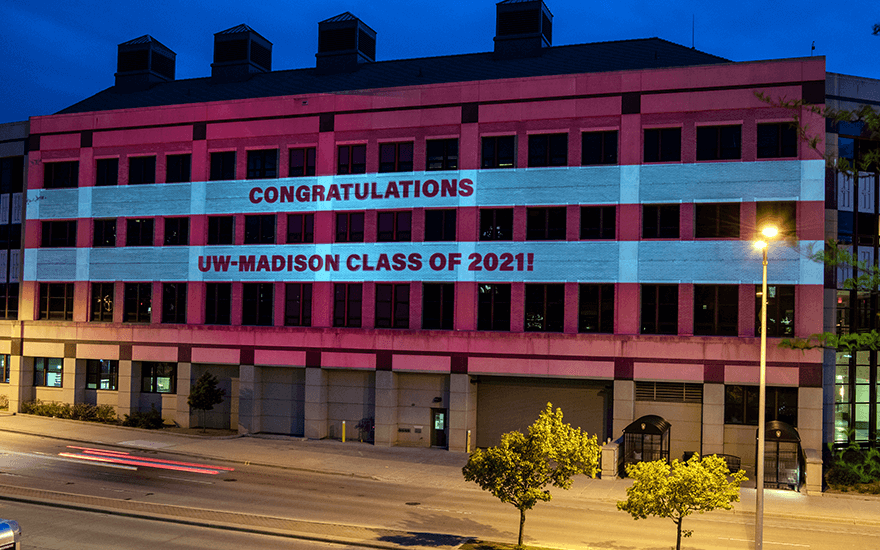 The exterior of Grainger Hall is illuminated with a light show to celebrate commencement