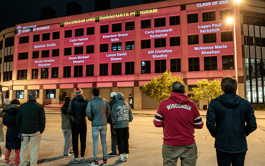 Observers watch a light show celebrating commencement on the exterior of Grainger Hall