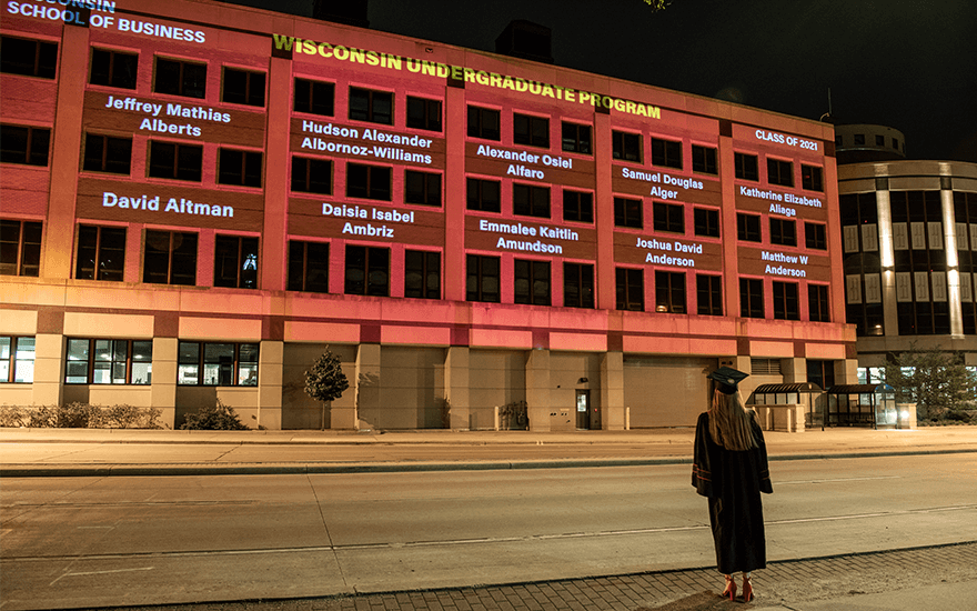 A graduate in cap and gown watches a light show celebrating commencement on the side of Grainger Hall