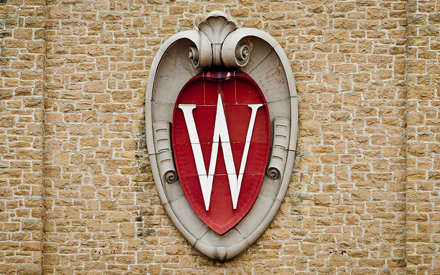 UW-Madison crest on a brick wall